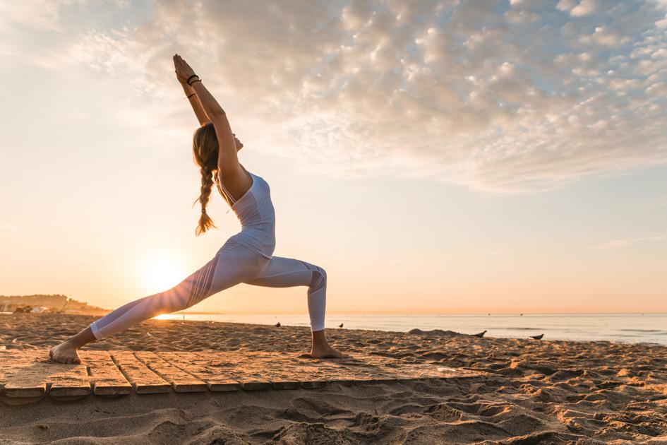 yoga trends, girl doing yoga on the beach