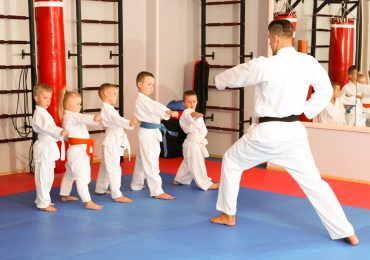 teaching children martial arts, karate instructor training little children in dojo