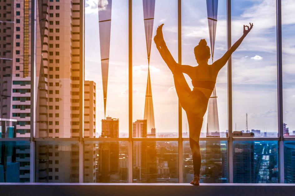 yoga studio marketing ideas, Woman practicing yoga on city view