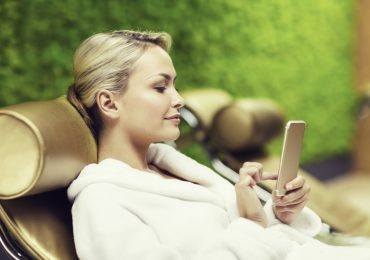 wellness center apps, woman at spa on phone