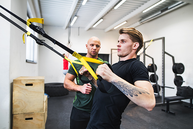 NPE, athlete with a personal trainer in gym doing exercise with TRX