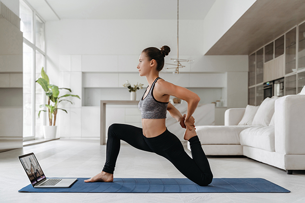 fitness studio, young woman doing fitness in her apartment with laptop