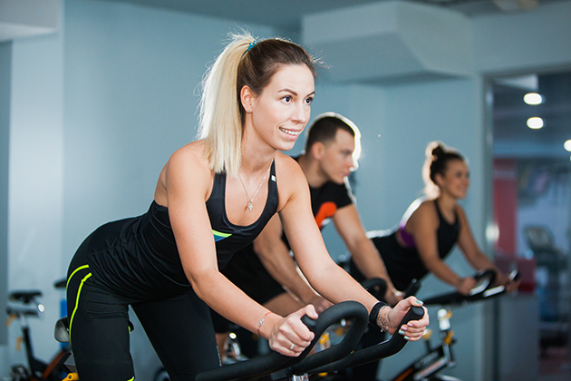 fitness studio, cycling class in fitness club, group of fit people spinning on cardio machine