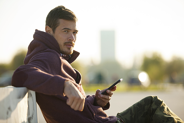 martial arts studio, man In hoodie holding mobile phone texting outdoors