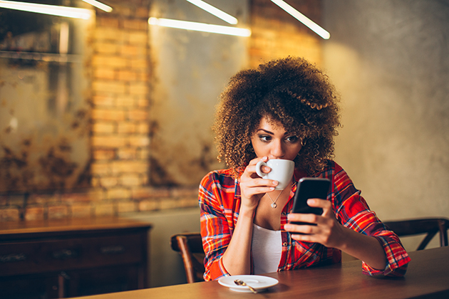 wellness center, young woman at cafe drinking coffee and using mobile phone