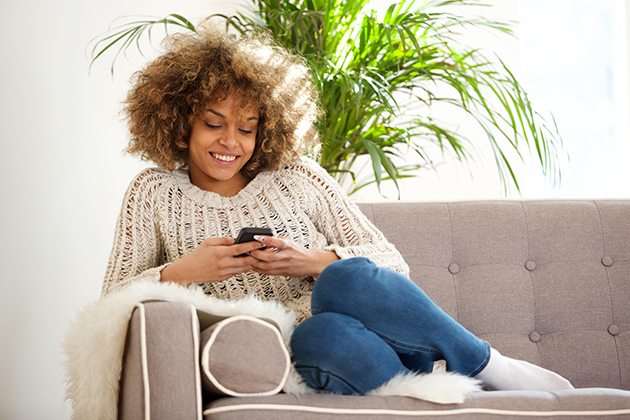 yoga studio, young african woman relaxing at home and using mobile phone
