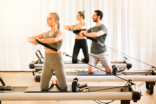 Pilates studio, group of people doing pilates torsion rotation exercises