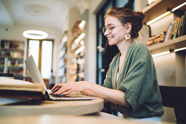 Pilates studio, cheerful young freelance woman typing on laptop in library