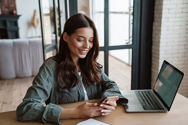 marketing strategies, beautiful smiling woman using cellphone while working with laptop