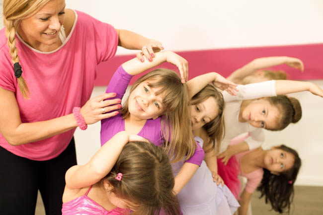 little girls in dance class, instructor helps dancers