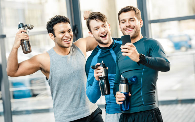 gym rewards program, three happy friends looking at phone