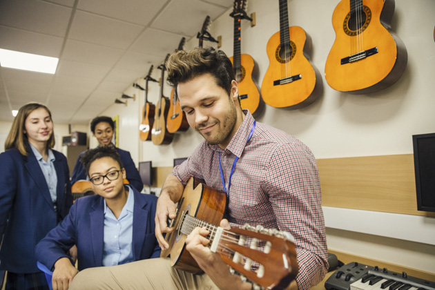 Music Instructors, music instructor teaching the guitar to multiple students