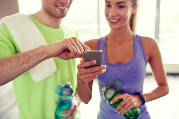new year's fitness resolutions, Happy client and personal trainer looking at phone