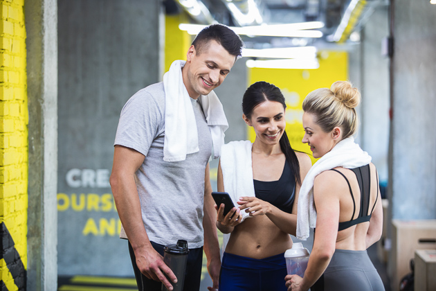 new year's fitness resolutions, gym buddies checking their phones