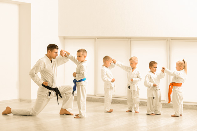 teaching children martial arts, little children with instructor practicing karate in dojo