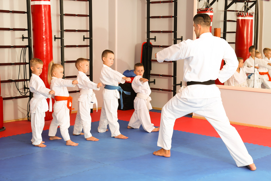 teaching children martial arts, karate instructor training little children in dojo