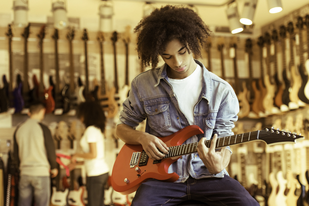 merchandise at your music school, Man playing electric guitar