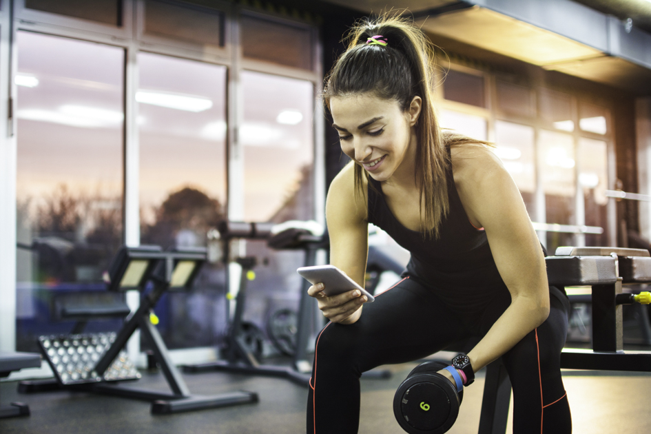 online gym software, woman at gym on the phone