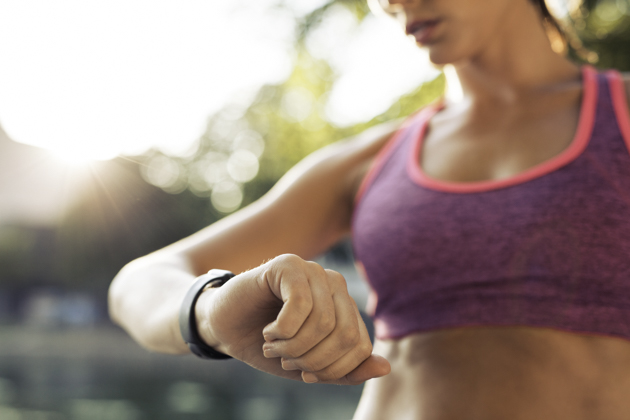 fitness industry technology trends, Runner checking her fitness smart watch device